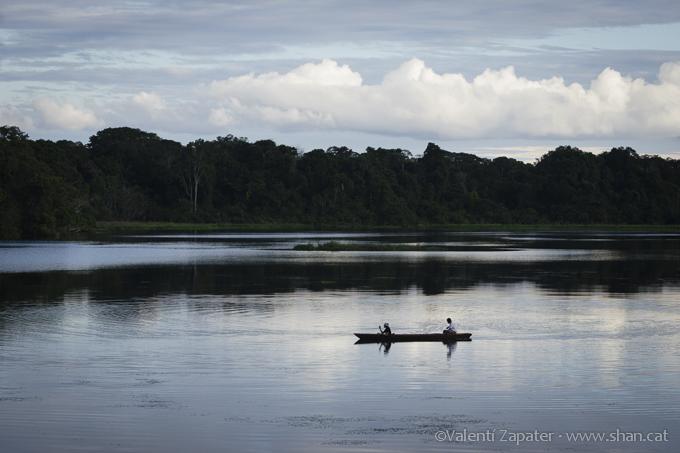 La calmada laguna de Hatuncocha y una canoa con dos personas remando. Parque Nacional Yasuní (Orellana, Ecuador)