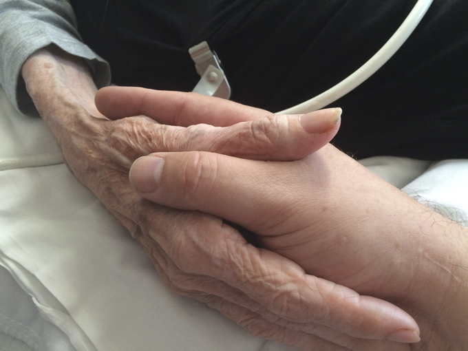 "Un hijo sostiene la mano de su madre en un ""hospice"". Tenía cáncer de ovarios avanzado y murió poco después de la toma de la fotografía. Holding the hand of my mother while she is in hospice care at a skilled nursing facility. She has advanced ovarian cancer. she died shortly after this photograph was taken. Oakland, California, June 2015. Author: Mercurywoodrose. CC BY-SA 4.0. File: https://commons.wikimedia.org/wiki/File:Mother_and_son_holding_hands.JPG"