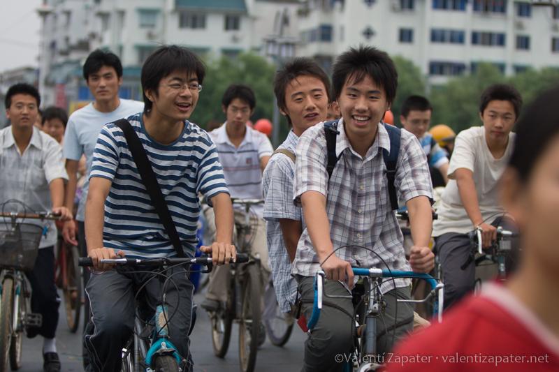 Jóvenes sonrientes desplazándose en bicicleta por la ciudad china de Tunxi (Huang Shan Shi)